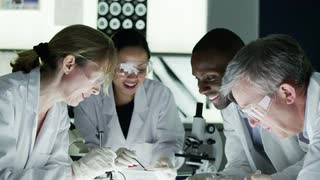 scientists-work-together-in-a-laboratory-then-smile-at-the-camera_7kffs2u7f__S0000